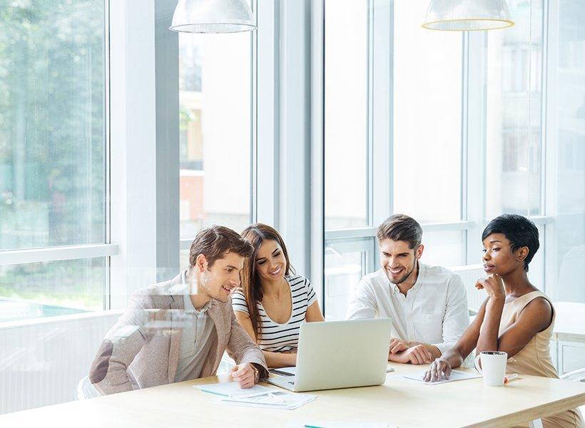Menschen schauen zusammen in einen Laptop.